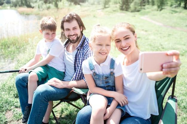 Mulher está sentada junto com sua família e tirando foto dela. todos eles estão olhando para a câmera e sorrindo. garotinho está sentado no colo do pai e segurando uma vara de peixe.