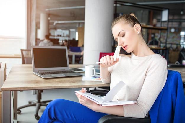 Mulher está sentada na cadeira em seu escritório e falando ao telefone. ela tem uma reunião por telefone. jovem é concentrada e séria.