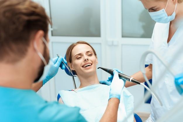 Mulher está sentada na cadeira odontológica, os médicos se inclinaram sobre ela