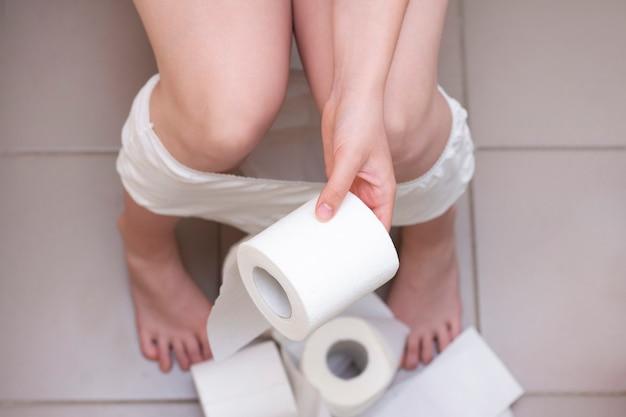 Mulher está sentada no vaso sanitário. muito papel higiênico no chão. mulher tem papel higiênico nas mãos dele.