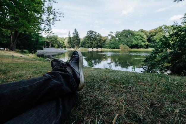 Mulher está sentada perto de uma lagoa no parque