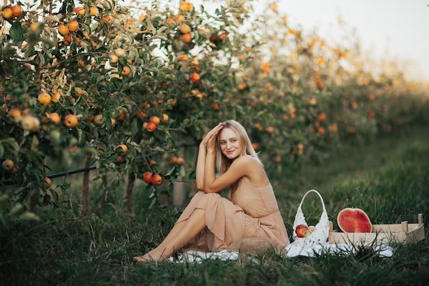 Mulher está sentada sobre um cobertor branco do lado de fora no pomar de maçãs. mulher feliz fazendo piquenique no jardim de outono com melancia, maçãs e uvas.