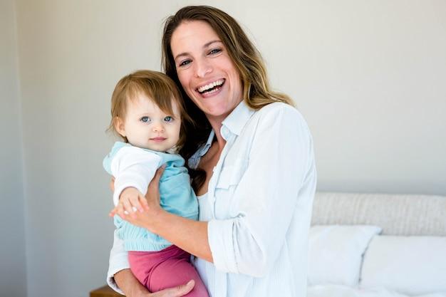 Mulher está sorrindo e segurando um bebê sorridente de olhos azuis
