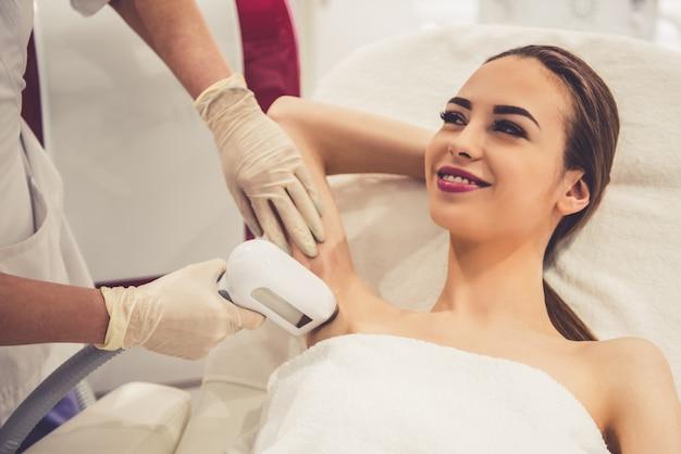 Mulher está sorrindo enquanto médico está fazendo a depilação a laser.