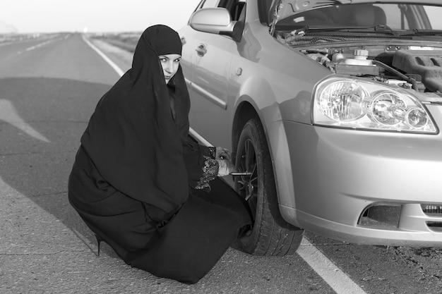 Mulher está substituindo uma roda de carro furada. preto e branco