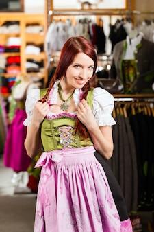 Mulher está tentando tracht ou dirndl em uma loja