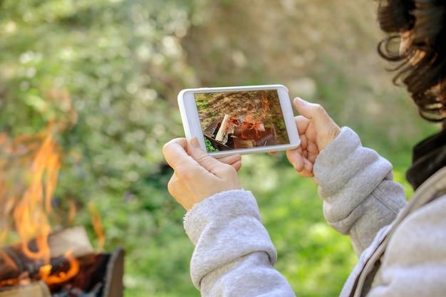 Mulher está tirando fotos do fogo em seu smartphone. ao ar livre.