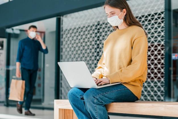 Mulher está trabalhando em um laptop enquanto está sentada do lado de fora de um prédio da cidade