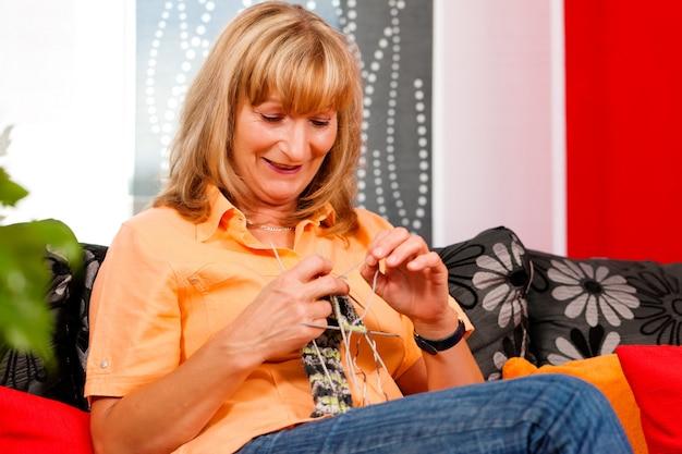 Mulher está tricotando em sua sala de estar