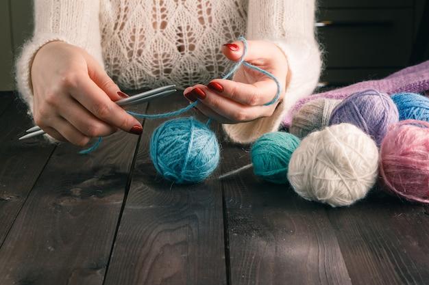 Mulher está tricotando em uma mesa de cozinha