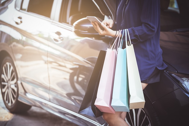 Mulher está usando telefone inteligente depois de fazer compras no shopping e em pé no parque de estacionamento