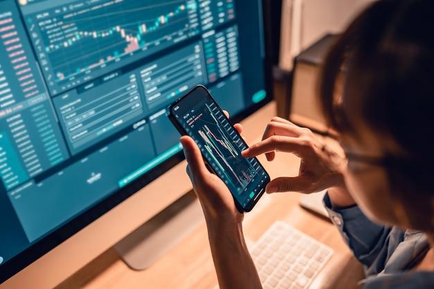 Mulher está verificando a tabela de preços do bitcoin na bolsa digital no smartphone