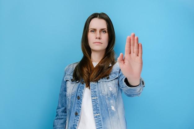 Mulher estende a palma da mão para a câmera, evitando que você cometa erros