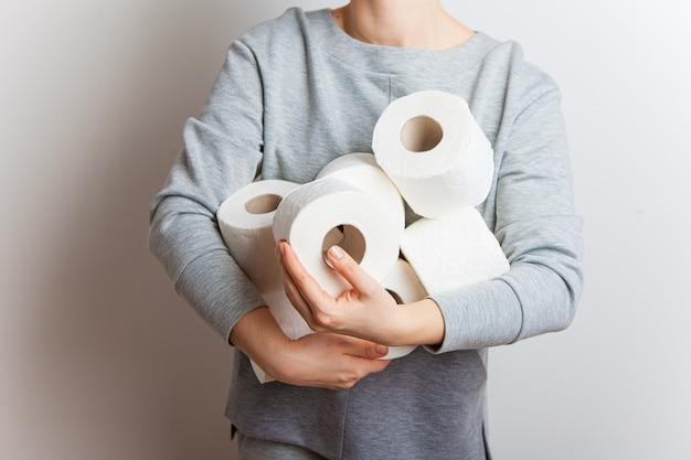 Mulher estende para a frente muitos rolos de papel higiênico.