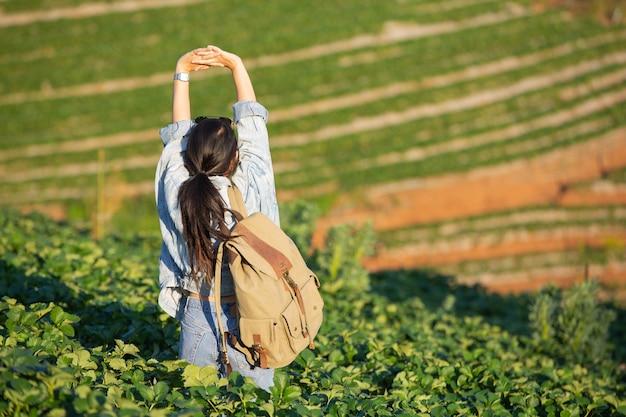 Mulher estendendo os braços em uma fazenda de morango