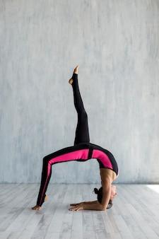 Mulher, estender, dela, perna, enquanto, fazendo, ponte, pose