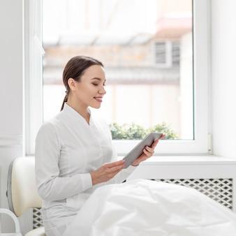 Mulher esteticista na clínica com tablet
