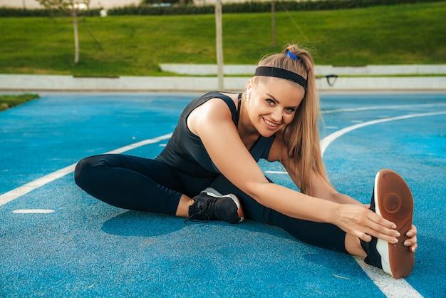 Mulher estica os músculos no ginásio ao ar livre