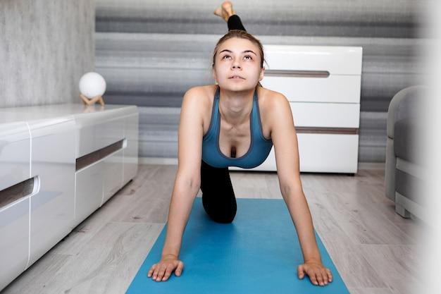 Mulher esticando a perna no tapete de ioga azul em casa na sala de estar
