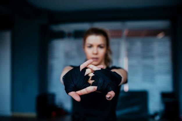 Mulher esticando as mãos com bandagem de boxe em direção à câmera.