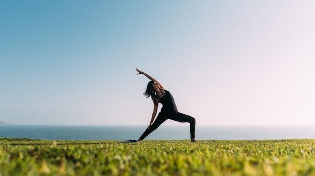 Mulher esticando o braço em um lugar natural, praticando ioga. copie o espaço