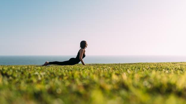 Mulher esticando o corpo deitado na grama ao ar livre à tarde. copie o espaço
