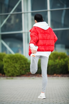 Mulher, esticando o corpo, fazendo exercícios na rua