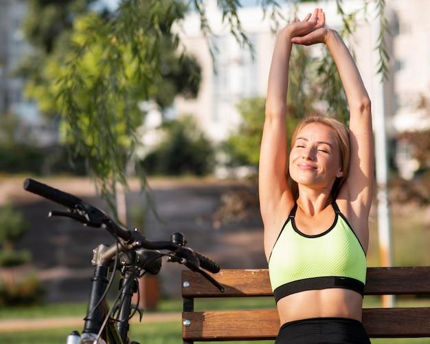 Mulher esticando os braços ao lado da bicicleta
