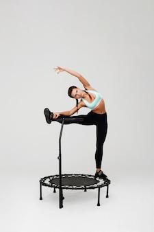Mulher, esticar, músculos, ficar, rebounder, com, perna alça