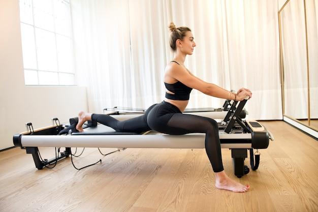 Mulher, esticar pernas, enquanto, em, exercite máquina