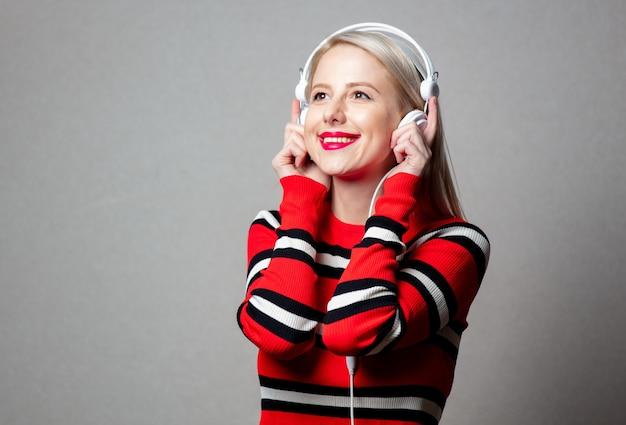 Mulher estilizada com suéter vermelho e fones de ouvido na parede cinza