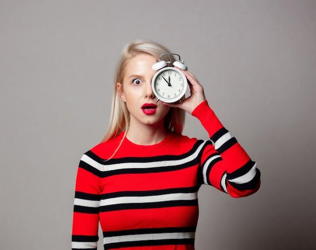 Mulher estilizada em um suéter vermelho com despertador na parede cinza