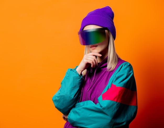 Mulher estilosa com agasalho de treino dos anos 90 com óculos vr laranja