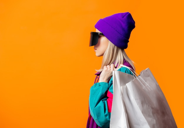 Mulher estilosa com agasalho de treino dos anos 90 e óculos de realidade virtual com sacolas de compras laranja