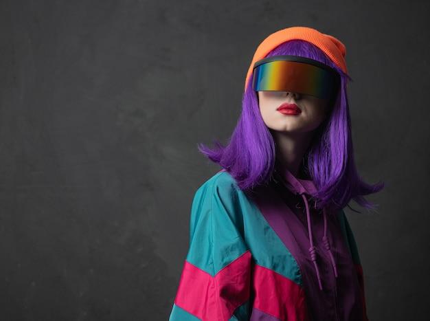 Mulher estilosa com agasalho esportivo dos anos 80 e óculos de realidade virtual