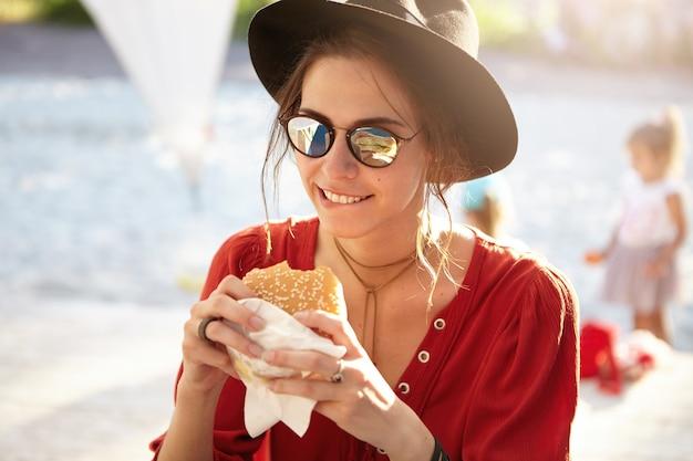 Mulher estilosa com blusa vermelha e chapéu grande