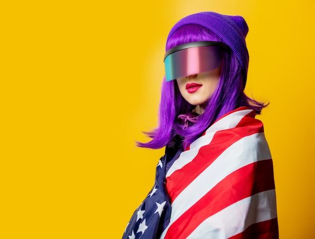 Mulher estilosa com óculos de realidade virtual e agasalho esportivo dos anos 80 com a bandeira dos eua na parede amarela