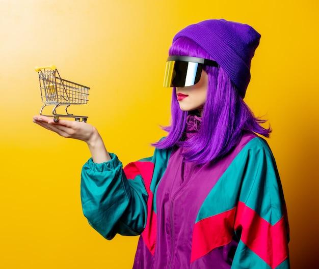 Mulher estilosa com óculos de realidade virtual e agasalho esportivo dos anos 80 com carrinho de compras na parede amarela