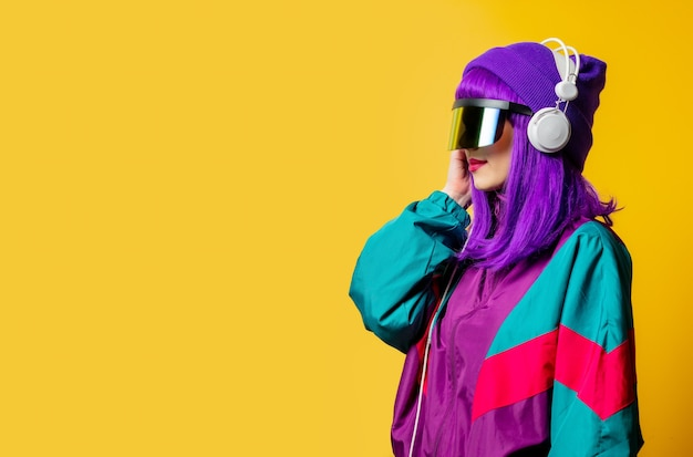 Mulher estilosa com óculos de realidade virtual e agasalho esportivo dos anos 80 com fones de ouvido na parede amarela