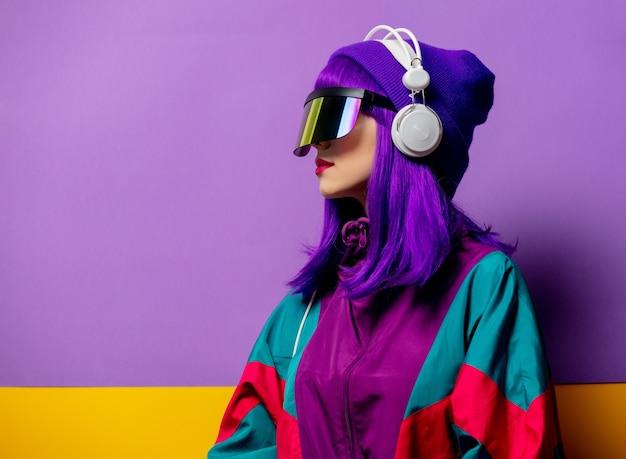 Mulher estilosa com óculos de realidade virtual e agasalho esportivo dos anos 80 com fones de ouvido na parede violeta