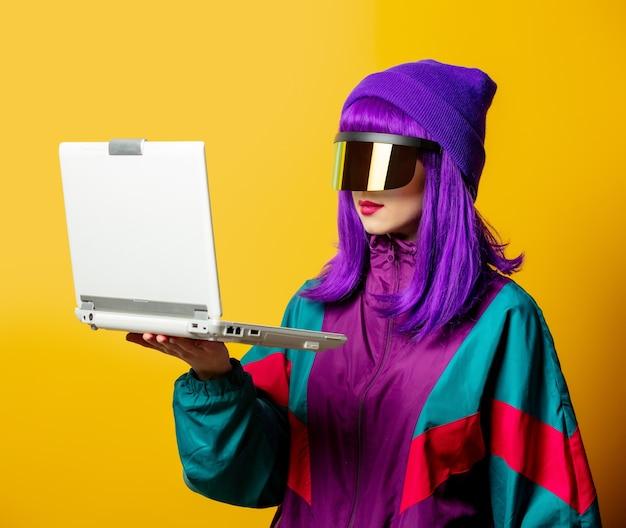 Mulher estilosa com óculos de realidade virtual e agasalho esportivo dos anos 80 com laptop na parede amarela