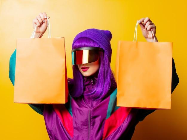 Mulher estilosa com óculos de realidade virtual e agasalho esportivo dos anos 80 com sacolas de compras na parede amarela