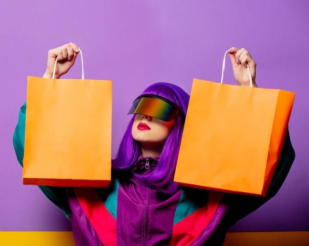 Mulher estilosa com óculos de realidade virtual e agasalho esportivo dos anos 80 com sacolas de compras na parede violeta