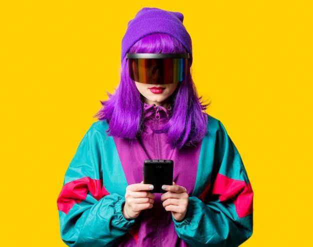 Mulher estilosa com óculos de realidade virtual e agasalho esportivo dos anos 80 com telefone celular na parede amarela