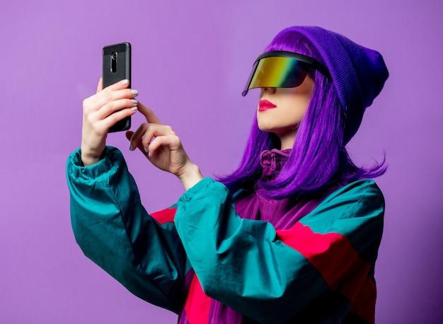 Mulher estilosa com óculos de realidade virtual e agasalho esportivo dos anos 80 com telefone celular na parede violeta
