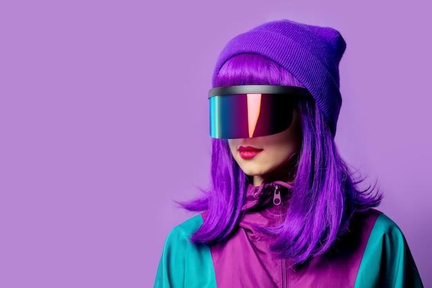 Mulher estilosa com óculos de realidade virtual e agasalho esportivo dos anos 80 na parede violeta
