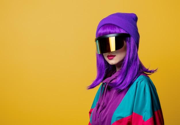 Mulher estilosa com óculos de rv e agasalho dos anos 80 na parede amarela