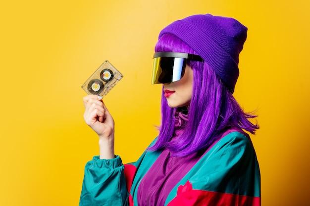 Mulher estilosa com óculos de rv e agasalho esportivo dos anos 80 com fita de áudio na parede amarela