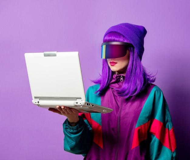 Mulher estilosa com óculos vr e agasalho dos anos 80 com laptop na parede violeta