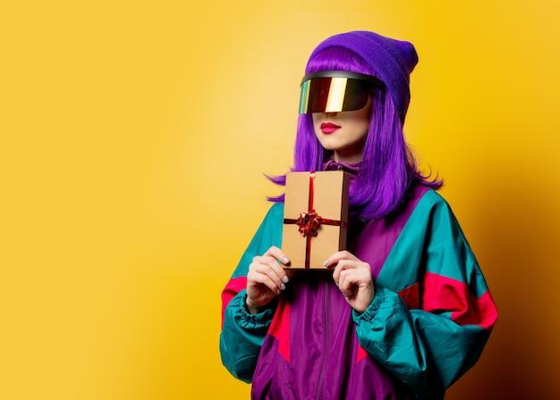 Mulher estilosa com óculos vr e agasalho esportivo dos anos 80 com caixa de presente na parede amarela